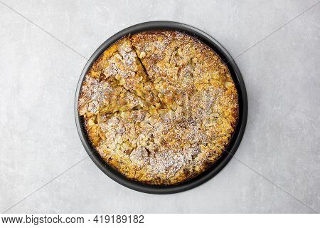 Almond Homemade Cake With Sliced Almonds Crust And Icing Powder Sugar On Light Gray Concrete Backgro