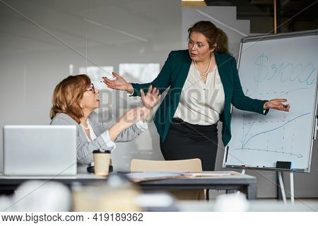 Woman And Her Supervisor Having A Heated Discussion Near Chart