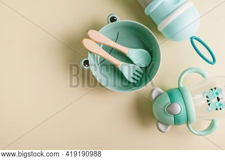 Baby Feeding Accessories. A Plate, A Spoon, A Fork, A Baby Milk Formula Feeding Bottle And A Jar For