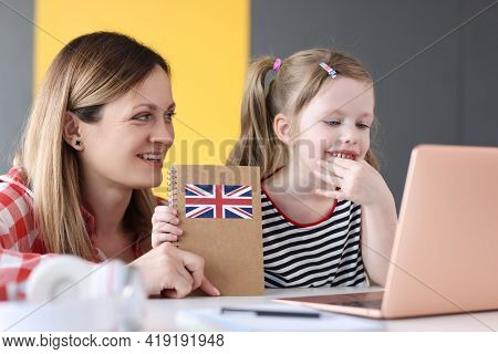 Little Girl And Mom Sitting In Front Of Laptop With English Textbooks