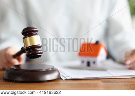 Judge Holding Wooden Hammer Near Toy Little House Closeup
