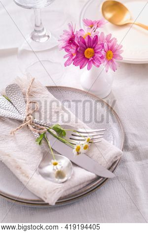 Cutlery with napkin and flower decoration - fine dining and place setting in white