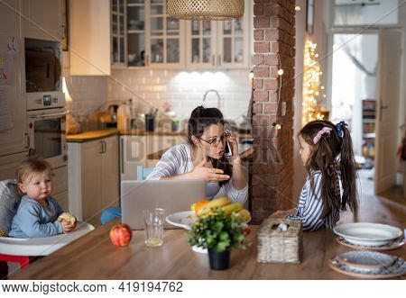 Angry Mother With Small Daughters In Kitchen, Home Office Concept.
