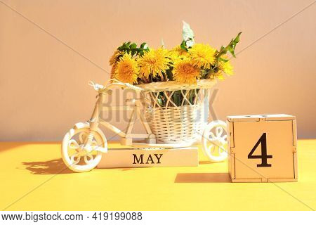 Calendar For May 4 : A Cube With The Number 4, The Name Of The Month Of May In English, A Bicycle Wi