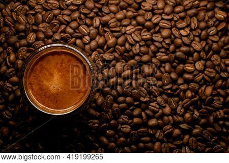 Beautiful Top View Of Glass With Foamy Coffee Drink On Coffee Beans Background