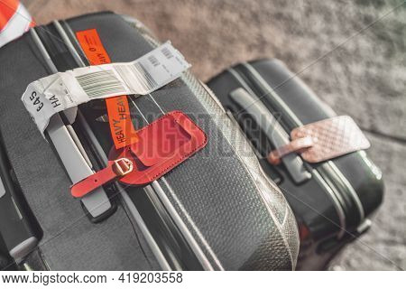 Two suitcases at airport with heavy tag closeup. Checked suitcase and carry-on luggage on the curbside ready for travel with address tags.