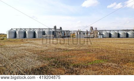 Wheat Storage Elevator. Silver Silos On Agro Manufacturing Plant For Processing Drying Cleaning And