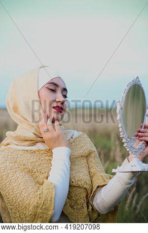 A Muslim Woman Is Sitting On The Grass And Hold A Two Rabbit In Her Arms. A Portrait Of A Muslim Wom