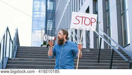 Single Protest Of Caucasian Man With Beard Talking And Screaming In Megaphone. Male Protestant Holdi