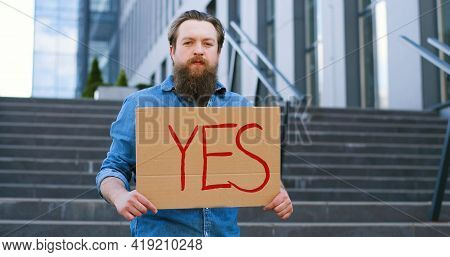 Portrait Shot Of Caucasian Male Activist With Beard Holding Poster Yes At Demonstration Or Protest.