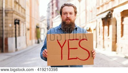 Portrait Shot Of Caucasian Young Man Standing On Street In Town And Showing Poster With Yes Word. Ma