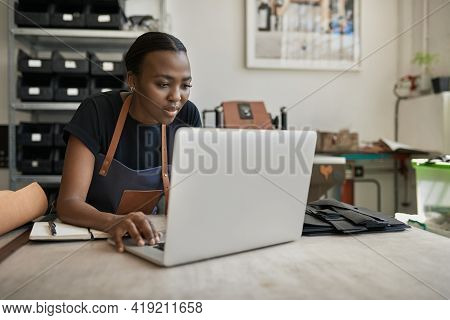 African Female Leather Worker Using A Laptop At A Workbench