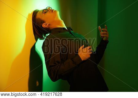 Feelings and emotions. Emotional young man stands, sad and alone, leaning against the wall in dark green and yellow lighting.