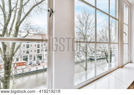 Amazing View Of River Near Leafless Trees And Residential Buildings From Window Of Contemporary Flat