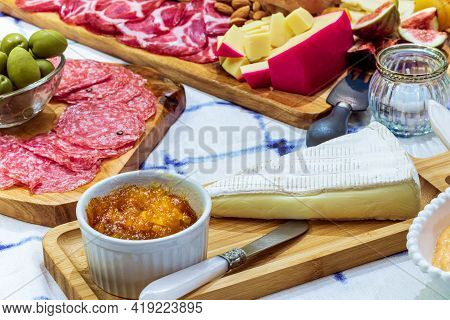 Different Types Of Cheeses, Wines, Baguettes, Fruits And Snacks On The Table For Tasting And Holiday