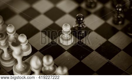Two Chess Pieces Are Pawns: Black And White. Wooden Chess Pieces On The Chessboard, Top View.. Intel