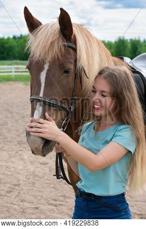 Portrait Of Smiling Young Woman With Blond Long Hair Is Caressing Brown Horse Snoot With Big Nostril