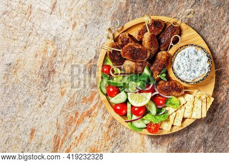Greek Lamb And Feta Kofta Skewers With Fresh Tomatoes, Mint, Red Onion Slices, Crackers, And Tzatzik