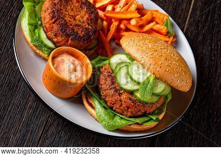 Harissa Lamb Burgers On Toasted Buns With Lettuce, Fresh Cucumber, Mayo Sauce And Carrot Chips On A