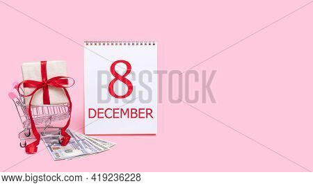8th Day Of December. A Gift Box In A Shopping Trolley, Dollars And A Calendar With The Date Of 8 Dec