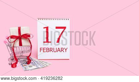 17th Day Of February. A Gift Box In A Shopping Trolley, Dollars And A Calendar With The Date Of 17 F