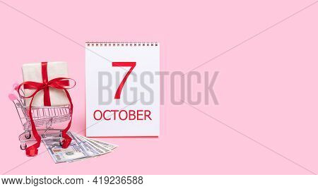 7th Day Of October. A Gift Box In A Shopping Trolley, Dollars And A Calendar With The Date Of 7 Octo
