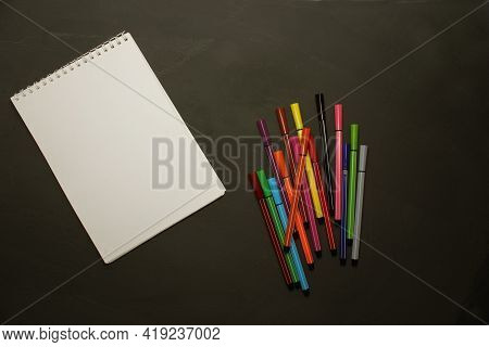 Markers Of Different Colors With A White Notebook On A Black Background. View From Above. Colorful P