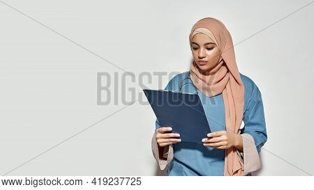 Young Arabian Woman Doctor With Stethoscope Looking Into Notepad While Posing On Light Background Wi