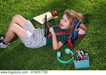 Kid With Tablet Device Sitting Outdoor In Garden, Wearing Short And Stripy Shirt. Lttle Child Outdoo