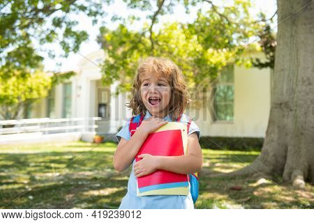 Back To School. Child With Rucksacks Standing In The Park Near School. Pupils With Books And Backpac
