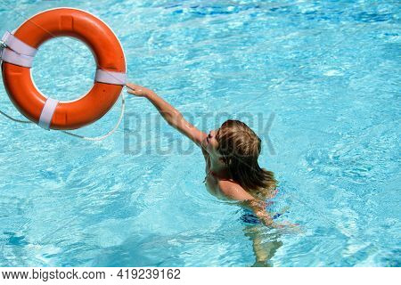 Child In Summer Pool. Summer Vacation. Happy Kid At Pool Party. Pool Resort. Rescue Ring In Swimming