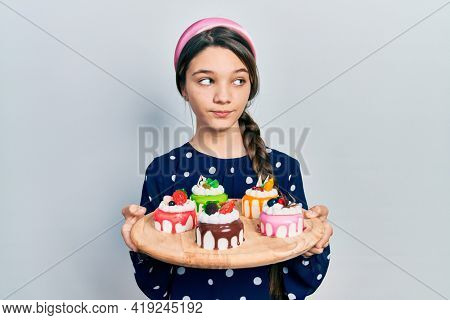 Young brunette girl holding sweet pastries smiling looking to the side and staring away thinking.
