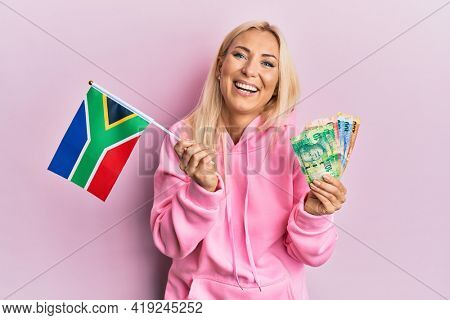 Young blonde woman holding south africa flag and rand banknotes smiling and laughing hard out loud because funny crazy joke.
