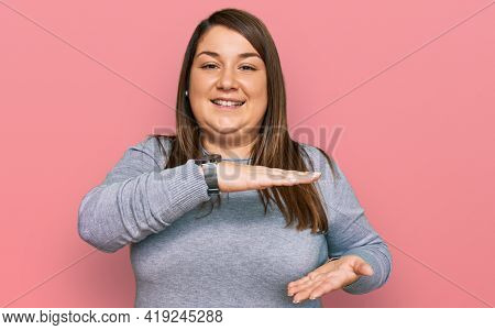 Beautiful brunette plus size woman wearing casual clothes gesturing with hands showing big and large size sign, measure symbol. smiling looking at the camera. measuring concept.