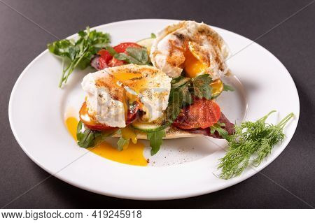 Macro Photo Of Poached Eggs. Spreading Yolk From Eggs. Poached Eggs On A White Plate. Front View.