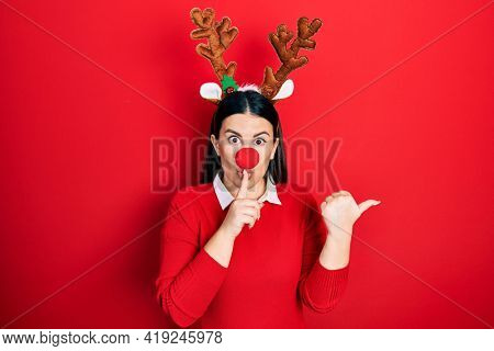 Young hispanic woman wearing deer christmas hat and red nose asking to be quiet with finger on lips pointing with hand to the side. silence and secret concept.