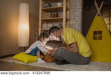 A Happy Father And His Little Daughter Are Surprised To Open A Wicker Surprise Box.