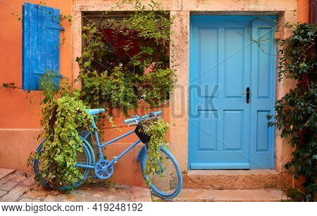 Rovinj, Istria, Croatia. Old blue ycle at street near door of entrance in house among green bushes and flowerpots with flowers. Picturesque cosy lane. Window shutters on windows.