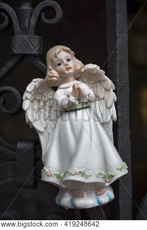 Figurine Of An Angel In A White Dress. Decorative Figure On A Metal Railings Background. Statuette.