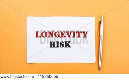 A Note With The Inscription Longevity Risk And A Pen. Long-term Risk. Pension Fund. Insurance Compan
