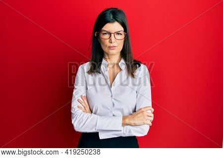 Young hispanic woman wearing business shirt and glasses skeptic and nervous, disapproving expression on face with crossed arms. negative person.