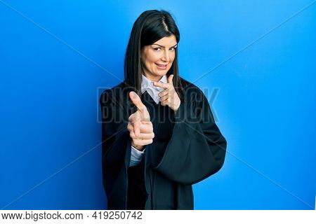 Young hispanic woman wearing judge uniform pointing fingers to camera with happy and funny face. good energy and vibes.
