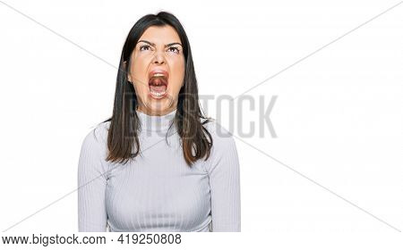 Beautiful brunette woman wearing casual clothes angry and mad screaming frustrated and furious, shouting with anger. rage and aggressive concept.