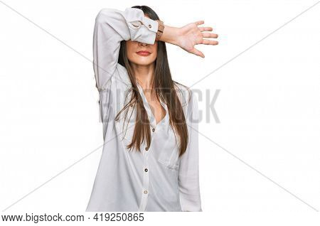 Young beautiful woman wearing casual white shirt covering eyes with arm, looking serious and sad. sightless, hiding and rejection concept