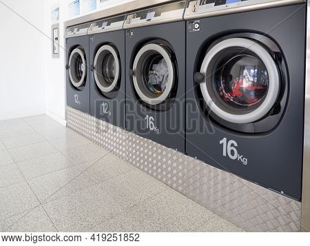 Row Of Washing Machines In A Public Laundromat. Cleaning Concept