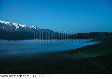 Atmospheric Mountains Landscape With Dense Fog And Great Snow Mountain Range Under Twilight Sky. Alp