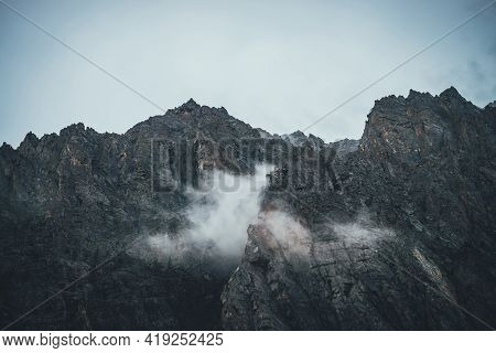 Atmospheric Mountain Landscape With Low Clouds On Sharp Rocks. Awesome Rocky Mountain With Pointy To