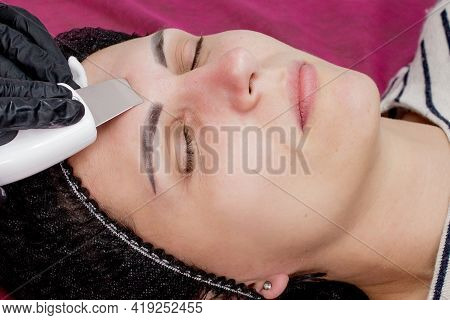 Young Woman Receiving Ultrasound Cavitation Facial Peeling Cleansing. Cosmetology Facial Skin Care T