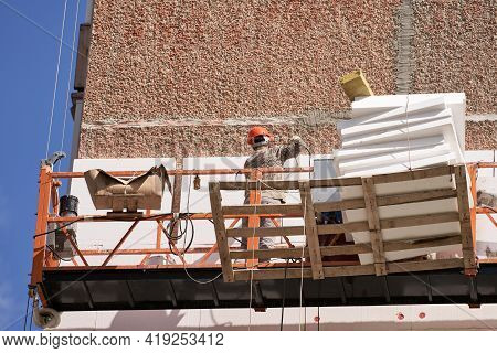 Insulation And Sound Insulation Of A Residential Building From The Outside. A Builder In A Lifting C