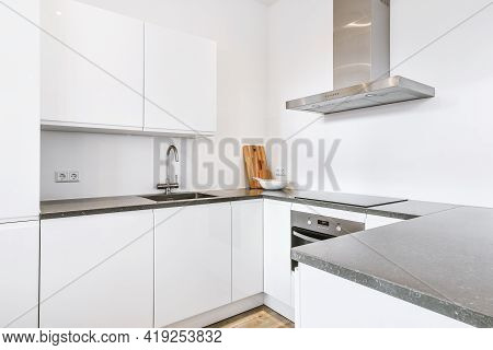 Simple White Cupboards With Sink And Appliances Located Under Exhaust Hood In Modern Kitchen At Home